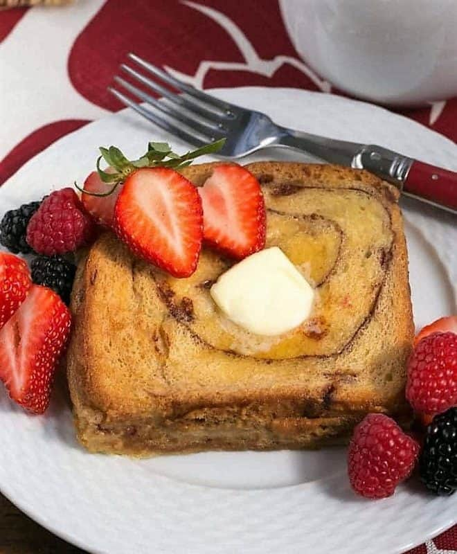 Overnight Cinnamon Bread French Toast on a white plate with a pate of butter and berries