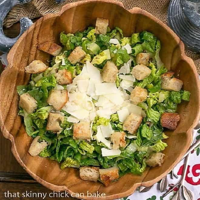 Perfect Caesar Salad in a wooden salad bowl with croutons and shaved Parmesan