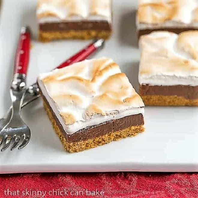 S'mores Fudge Bars on a square white platter with forks on a red napkin