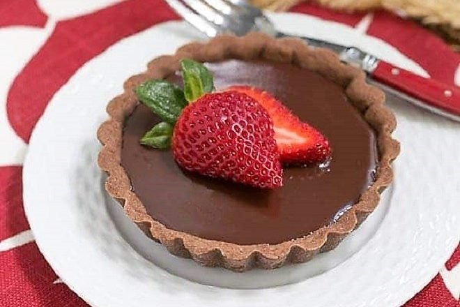 Double Chocolate Tartlet toped with a strawberry on a white plate