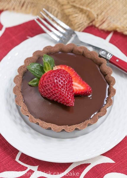 A Double Chocolate Tartlets on a white dessert plate with a red handled fork