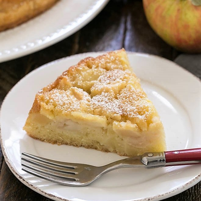 Slice of French Apple Cake on a round dessert plate
