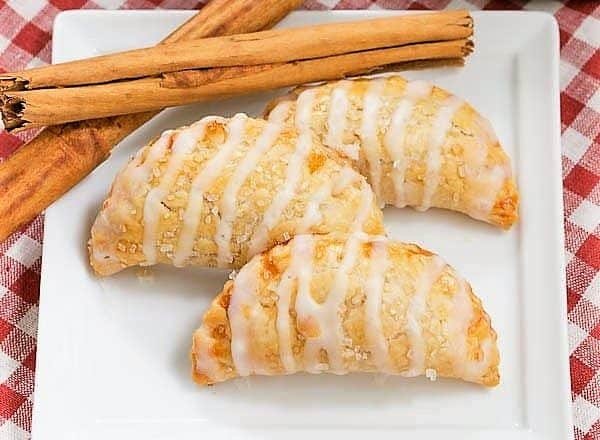 Fried Apple Pies on a white square plate with cinnamon sticks