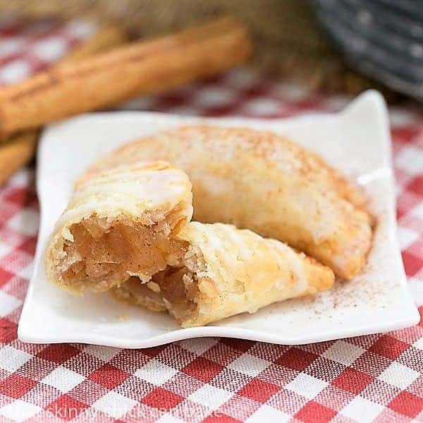 Two Fried Apple Pies on a ceramic plate, with one broken open to expose the filling