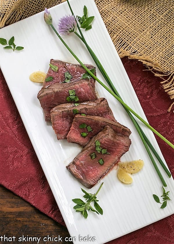 Grilled Tenderloin with Garlic Herb Butter on a platter with whole chive flowers