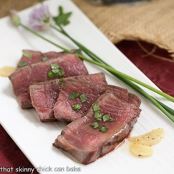 Sliced Grilled Tenderloin with Garlic Herb Butter sliced on a white platter