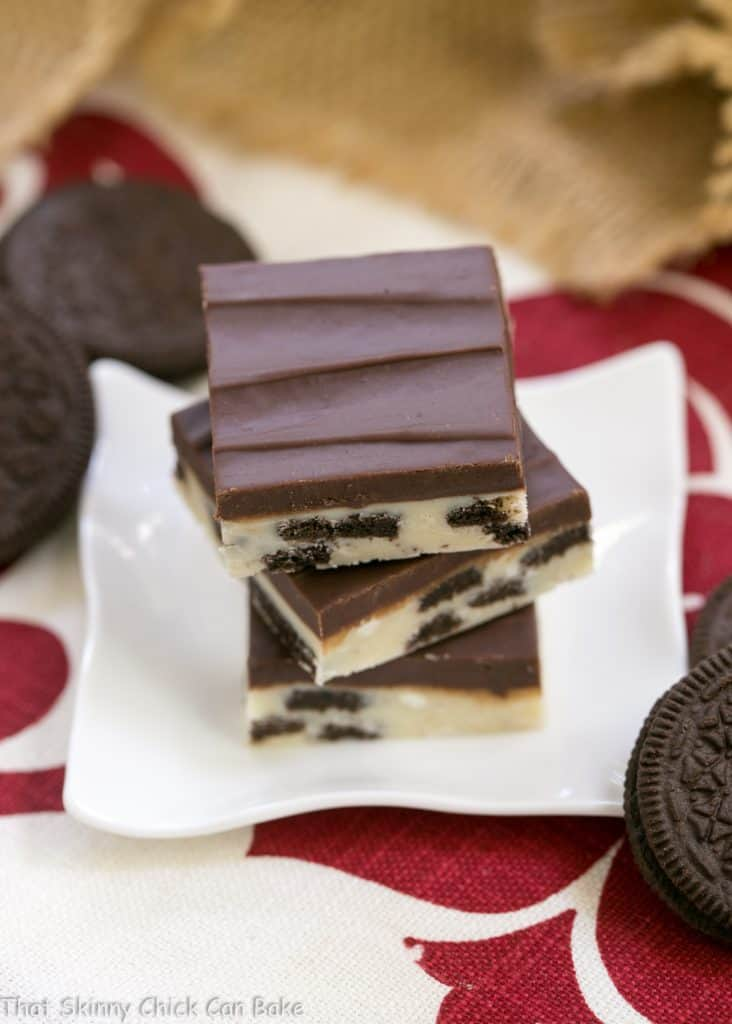 Oreo Double Decker Fudge stacked on a small white ceramic plate surrounded by Oreos