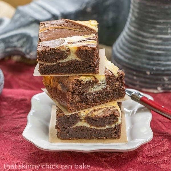 A stack of three Ricotta Cheesecake Brownies on a square white plate