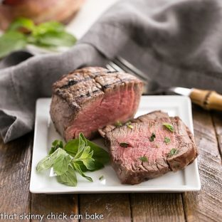 Grilled Steak with Garlic Butter and garnished with herbs on a square white plate