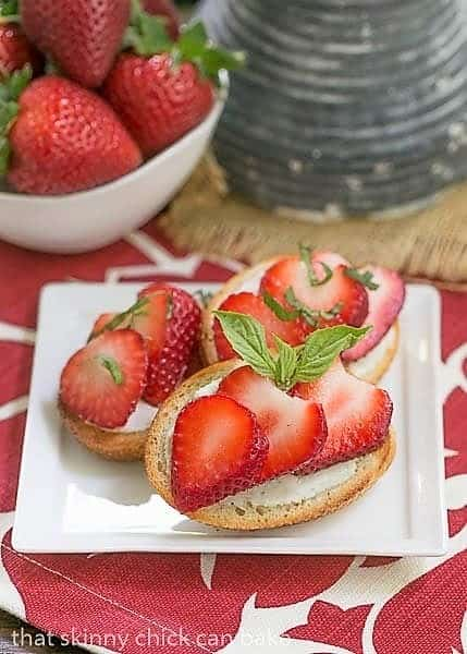 Strawberry Basil Crostini on a white appetizer plate with a bowl of strawberries
