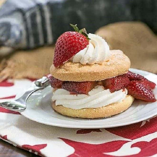 Strawberry Shortcake Franco American Style on a white dessert plate topped with roasted berries and cream