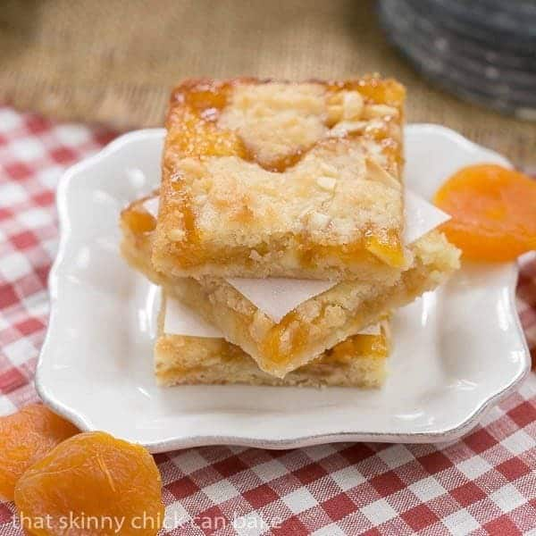 Apricot Bars stacked on a small, square white plate with dried apricot garnishes