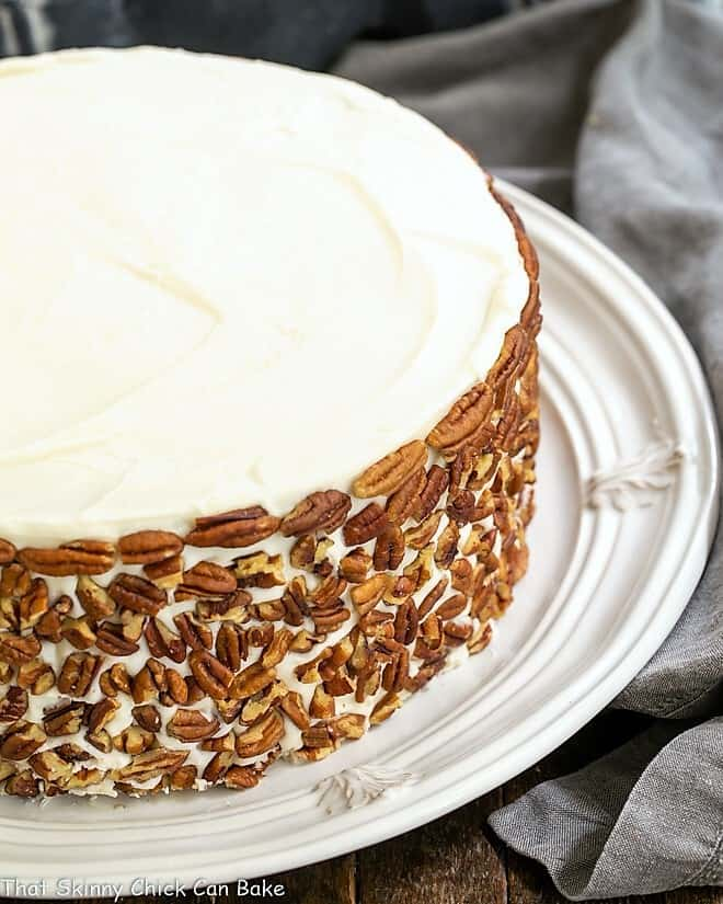 Classic Carrot Cake with pecans on the sides on a white serving plate