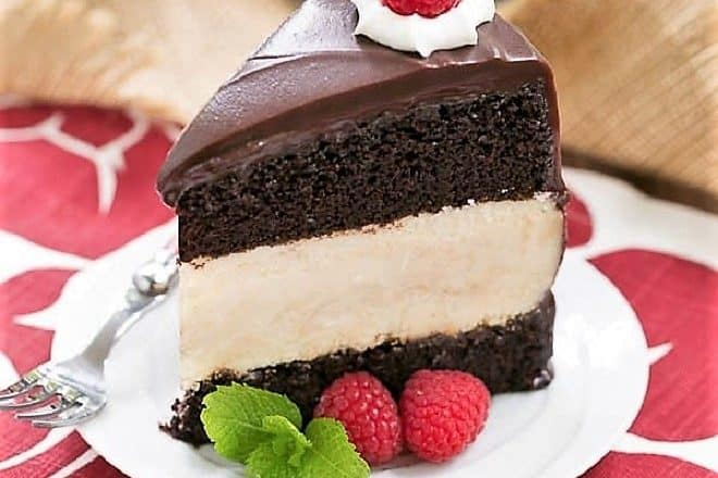 Slice of Cheesecake Filled Chocolate Cake on a white dessert plate