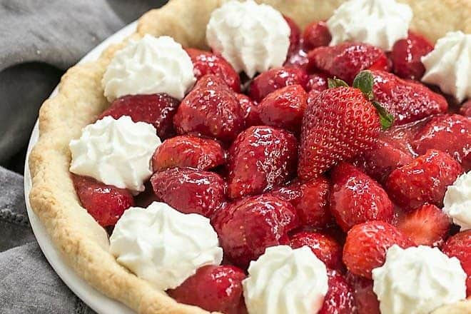 Simple strawberry pie in a white pie plate topped with dollops of whipped cream