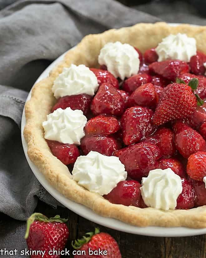 Fresh Strawberry Pie in a white pie plate next to a few fresh strawberries