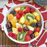 Honey Lime Fruit salad in a white serving bowl over and red and white napkin