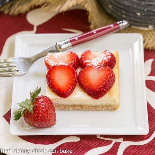 Strawberry Cheesecake Bars | A shortbread cookie crust topped with a thin layer of cheesecake and juicy sliced berries