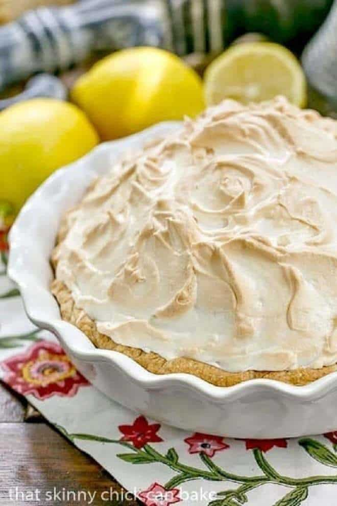 Mile High Lemon Meringue Pie in a white ceramic pie plate with lemons in the background