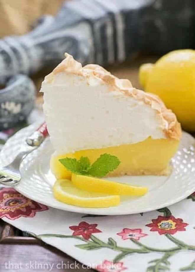 Mile High Lemon Meringue Pie slice garnished with mint and lemon slices