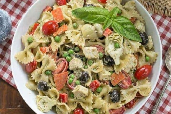 Overhead view of an Italian Pesto Pasta Salad in a white bowl over a checked napkin