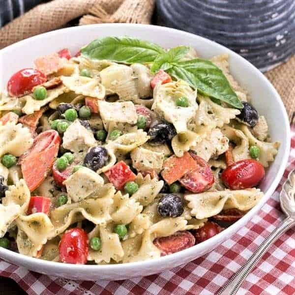 Pesto Pasta Salad in a flat white serving bowl with a silver serving spoon