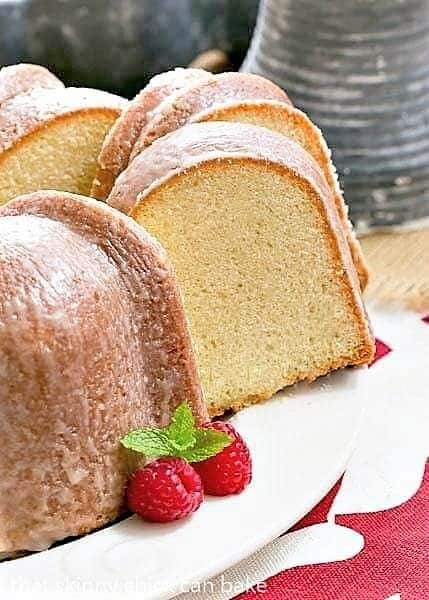 Sour Cream Pound Cake on a white cake plate with two slices pulled out of the whole cake