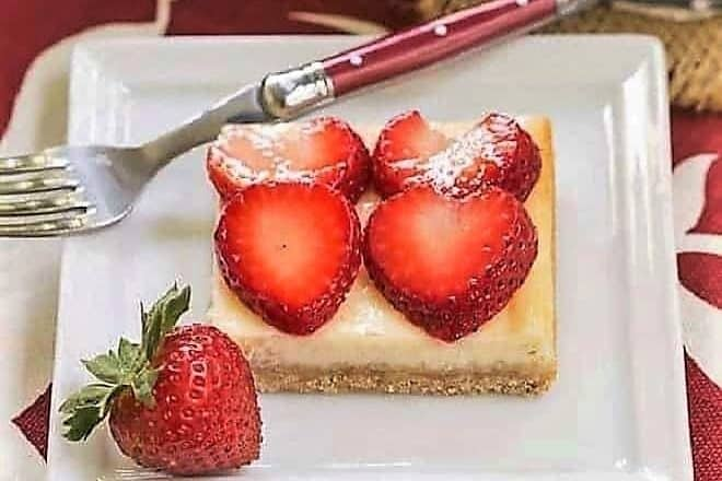 Strawberry Cheesecake Bars on a square plate with a red handled fork