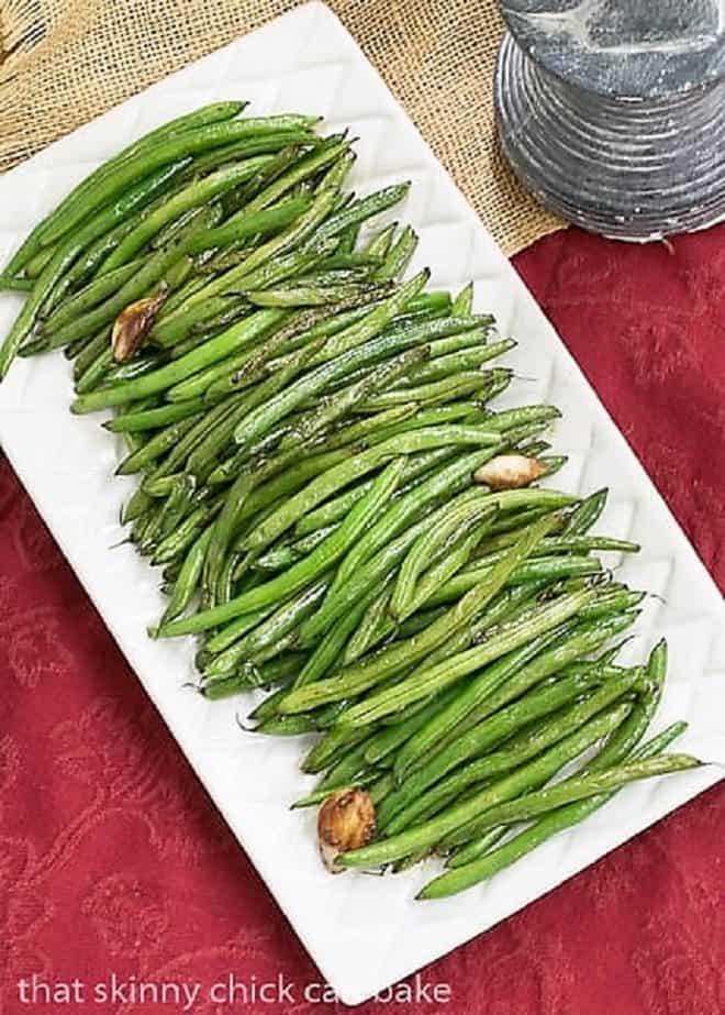 Asian Green Beans on a rectangular white platter on a red napkin