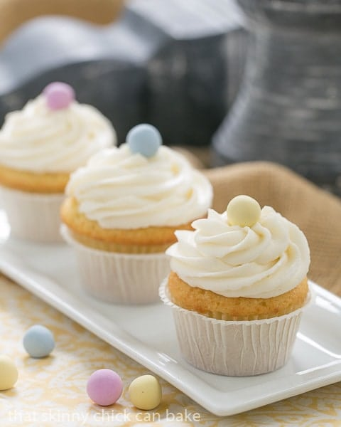 Buttercream Topped Vanilla Cupcakes lined up on a narrow white ceramic tray