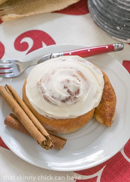 Old Fashioned Cinnamon Roll on a white plate with a red handled fork