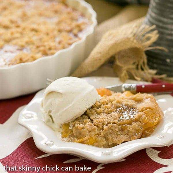 Classic Peach Crisp on an octagonal white plate with a scoop of vanilla ice cream