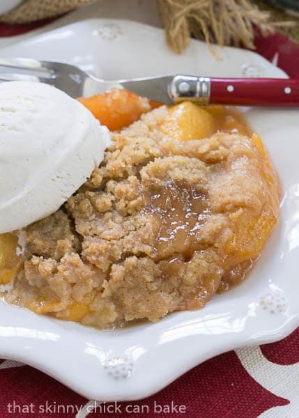 Classic Peach Crisp on a white dessert plate with a scoop of ice cream