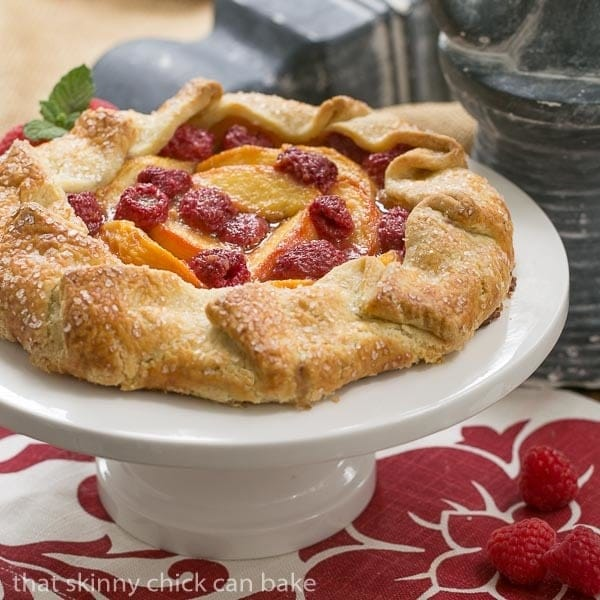 Peach Raspberry Galette on a white ceramic cake stand on a red and white napkin