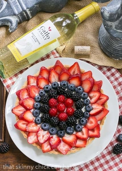 Summer Fruit Tart on a white plate with a bottle of white wine