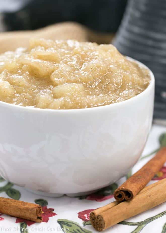 Side view of Cinnamon Spiced Applesauce  in a white bowl with cinnamon sticks