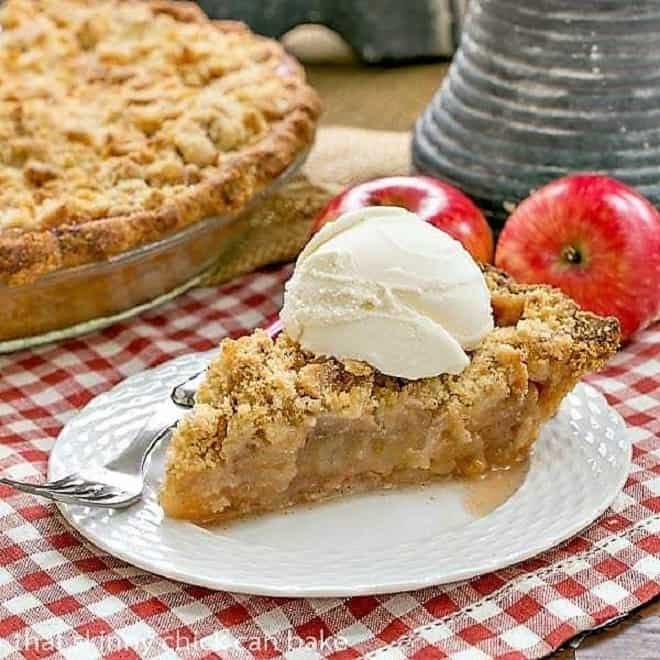 Slice of Dutch Apple Pie topped with a scoop of ice cream on a white dessert plate