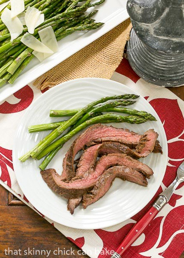 Overhead view of Easy Grilled Flank Steak on a dinner plate with asparagus spears