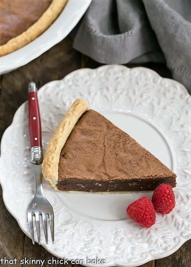 Fudgy Brownie Pie on a fancy white plate with raspberries and a red handled fork