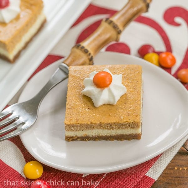 Pumpkin Cheesecake Bars | Biscoff crust topped with a layer of plain then pumpkin cheesecake!