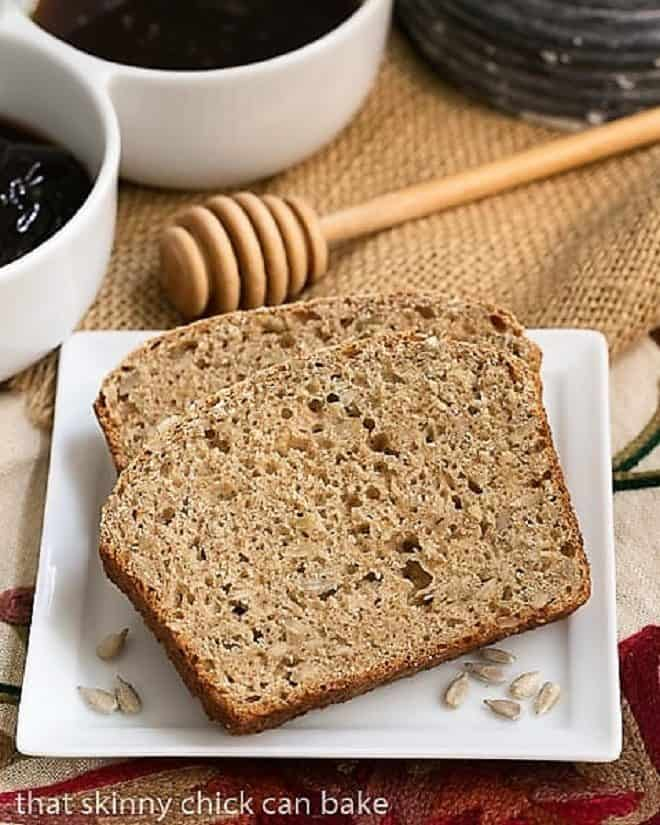 Sunflower Whole Wheat Bread slices on a square white plate with jelly