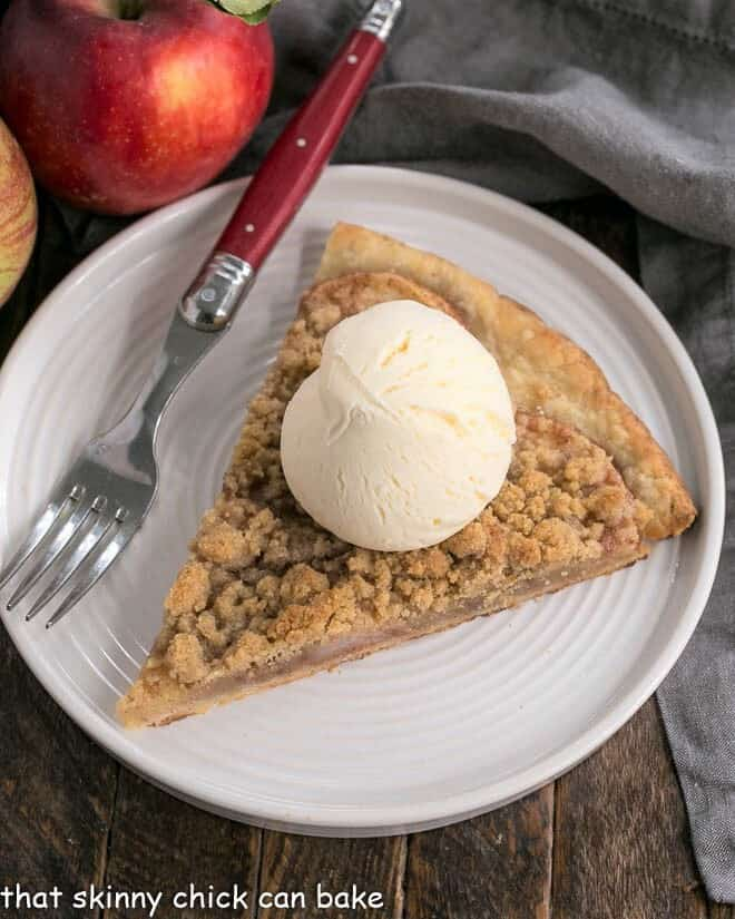A slice of apple pie pizza on a white plate topped with a scoop of ice cream