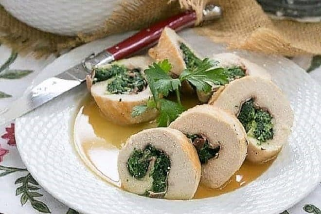 Chicken Spinach and Prosciutto Pinwheels on a white ceramic basket weave plate with a red knife