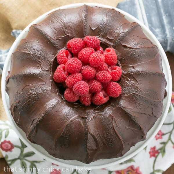 Chocolate Buttermilk Bundt Cake on a white cake stand garnished with fresh raspberries