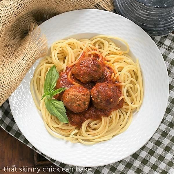 Overhead view of Classic Italian Meat Sauce over pasta and meatballs in a white bowl