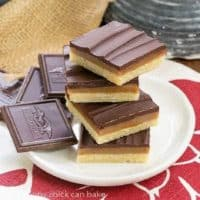 Ganache Topped Caramel Bars stacked on a round white plate