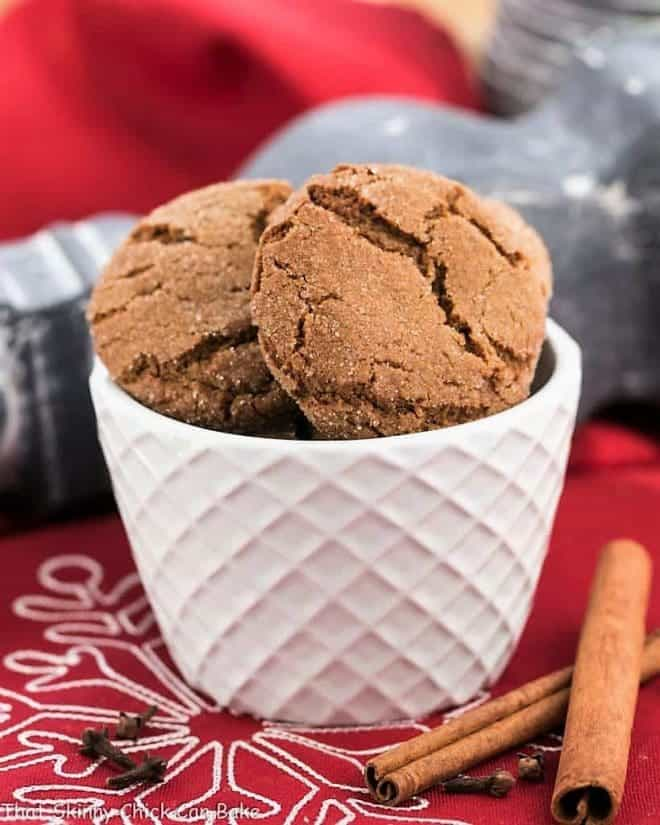 Chewy gingersnaps in a white bowl with cinnamon sticks and cloves