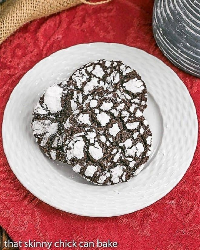 Three Chocolate Crinkles  on a white basketweave plate over a red napkin