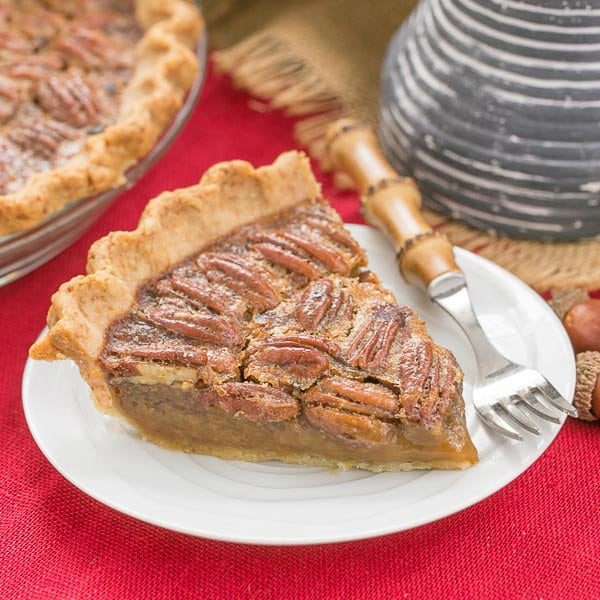 Classic Pecan Pie slice on a dessert plate over a red woven napkin