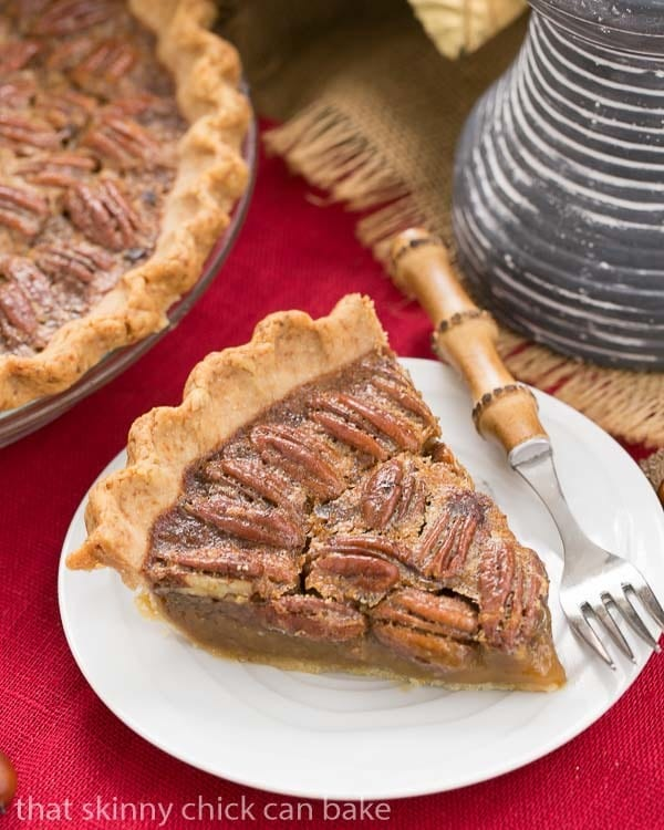 Classic Pecan Pie slice on a white dessert plate with a bamboo handle fork